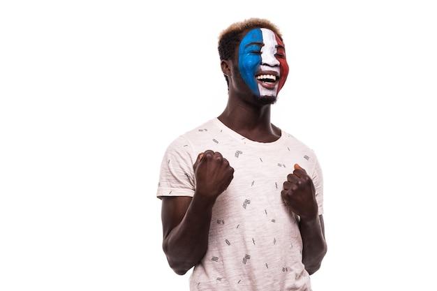 Счастливый победный крик афро-болельщик поддерживает сборную франции с раскрашенным лицом на белом фоне Бесплатные Фотографии