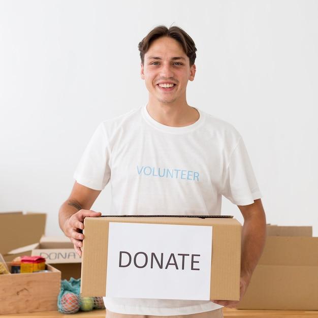 Счастливый волонтер держит коробку для пожертвований Бесплатные Фотографии