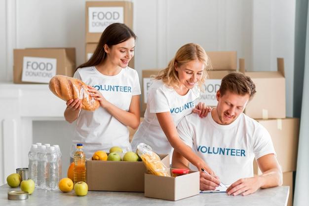 Volontari felici che aiutano con donazioni di cibo Foto Gratuite