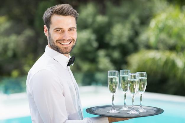 トレイにシャンパンフルートを運ぶ幸せなウェイター Premium写真