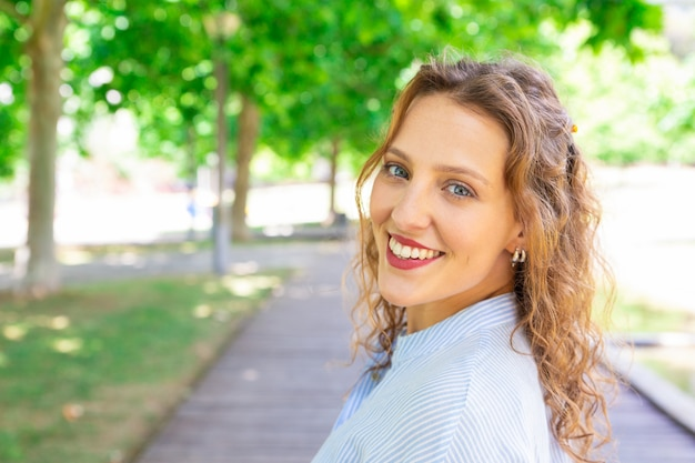 Happy wavy-haired girl smiling at camera outdoors Free Photo