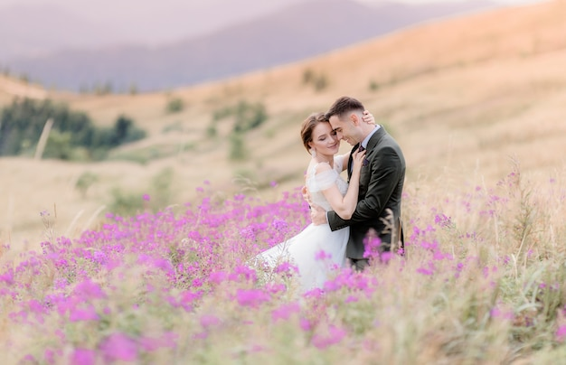 Happy wedding couple  is sitting on the hill of the meadow surrounded with pink flowers Free Photo