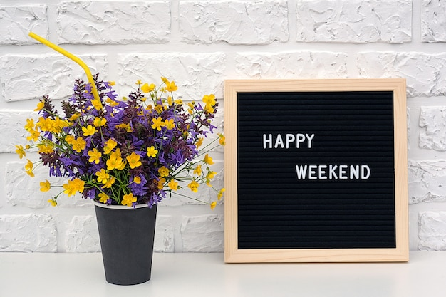 Happy weekend words on black letter board and bouquet of yellow dandelions flowers Premium Photo