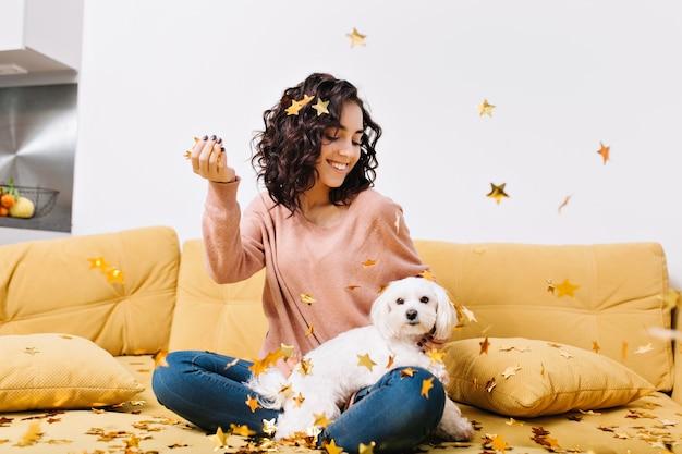 幸せな週末、モダンなアパートメントのソファの上の落下の黄金のティンセルで小さな犬を楽しんでいるカットの巻き毛を持つ若いうれしそうな女性の真の肯定的な感情 無料写真