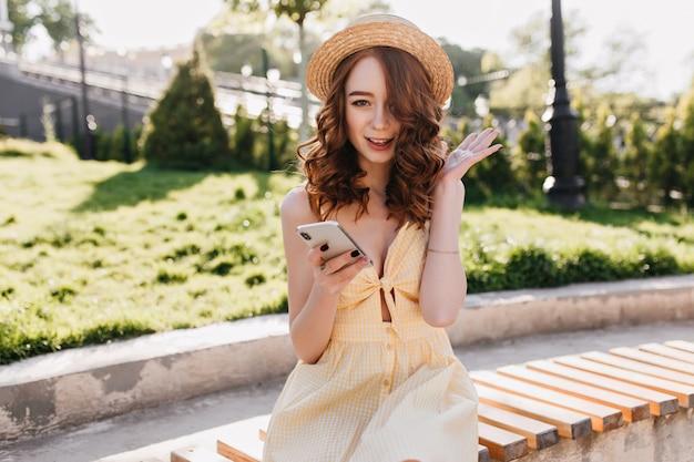 Счастливая обаятельная девушка с волнистыми рыжими волосами, сидя на скамейке с телефоном. открытый портрет восторженной женщины имбиря, проводящей утро в парке. Бесплатные Фотографии