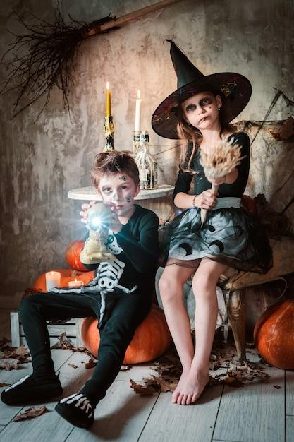 Счастливая девочка и мальчики ведьмы на хэллоуин. Premium Фотографии