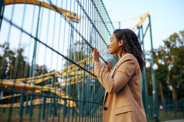 놀이 공원에서 롤러 코스터 매력에 행복 한 여자. 사랑 부부는 야외에서 휴식을 취하십시오. 여름철 가족 레저, 엔터테인먼트 테마 프리미엄 사진