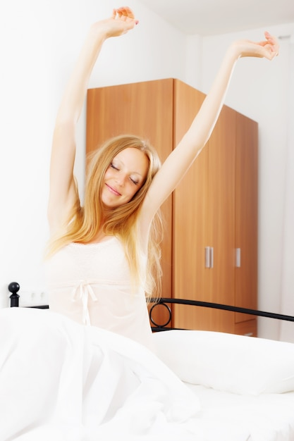 Happy woman awaking  in her bed Free Photo