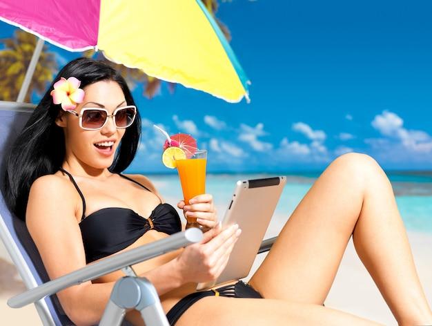 Donna felice sulla spiaggia con ipad. Foto Gratuite