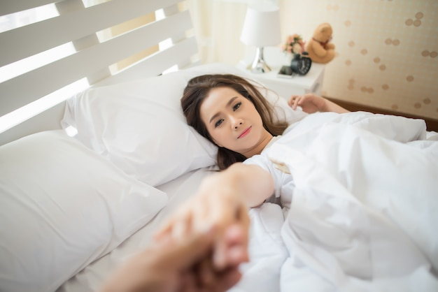 Happy woman on the bed and invited her boyfriend make something Free Photo