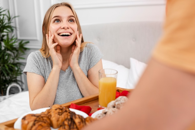 Happy woman being surprised with breakfast in bed Free Photo