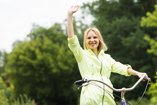 Happy woman on bicycle waving Free Photo