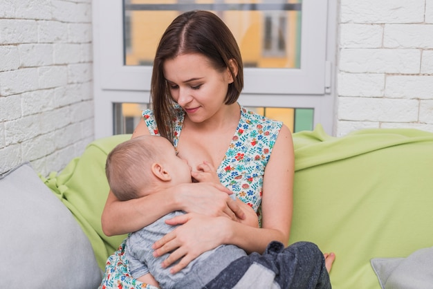 Happy woman breastfeeding her son Free Photo