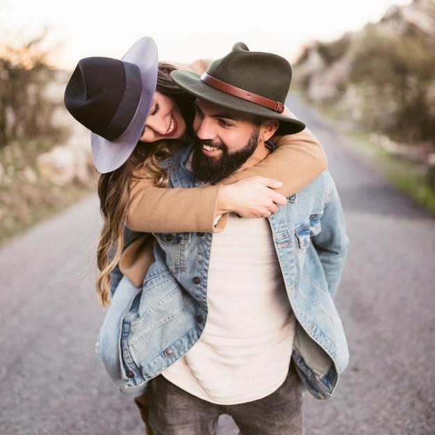 Happy woman carried on boyfriend back Free Photo