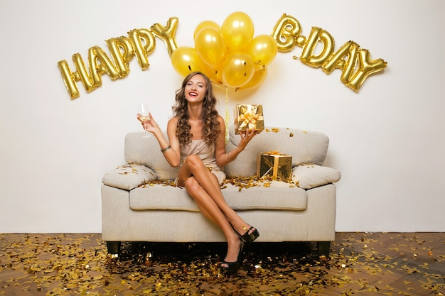 Happy woman celebrating birthday in golden confetti sitting on sofa Free Photo