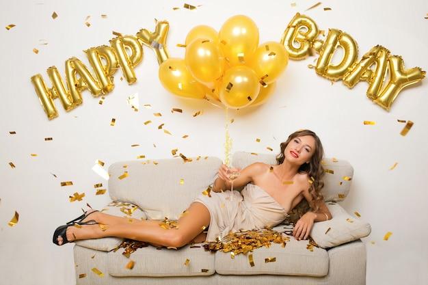 ソファーに座っていた金色の紙吹雪で誕生日を祝う幸せな女 無料写真