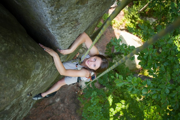 Happy woman climbing on a rocky wall rope, bouldering Premium Photo