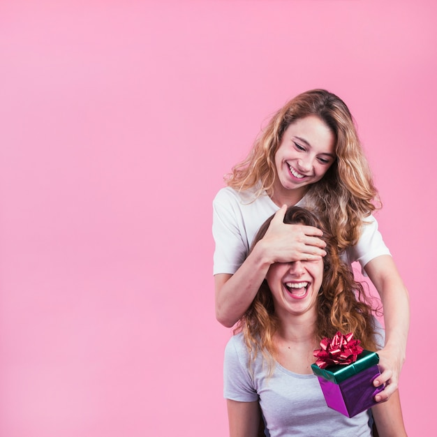Happy woman covering her female eyes holding gift box against pink background Free Photo
