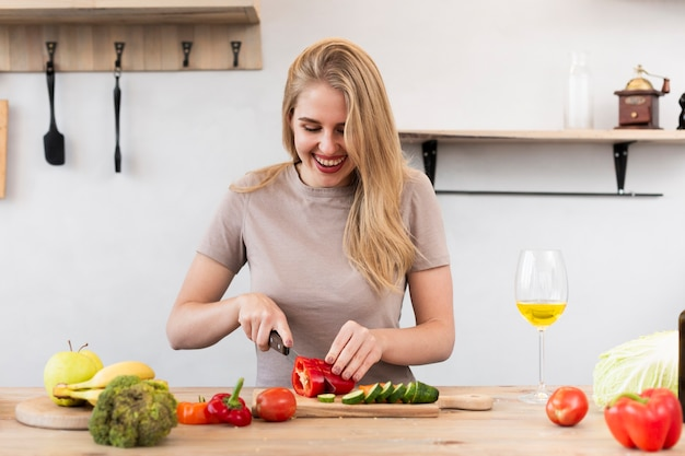 Happy woman cutting vegetables Free Photo
