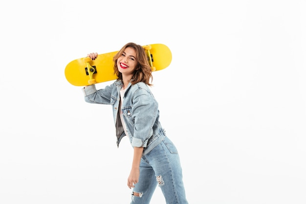 Happy woman in denim clothes posing with skateboard  over white wall Free Photo