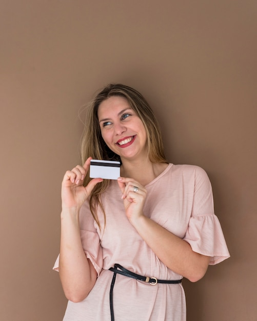 Happy woman in dress standing with credit card Free Photo