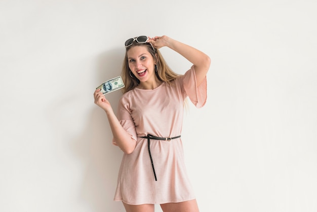 Happy woman in dress standing with money Free Photo