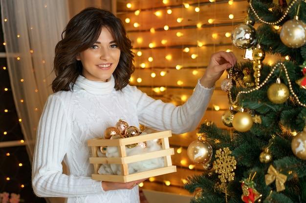 Happy woman dresses up a festive christmas tree, hangs balls Premium Photo
