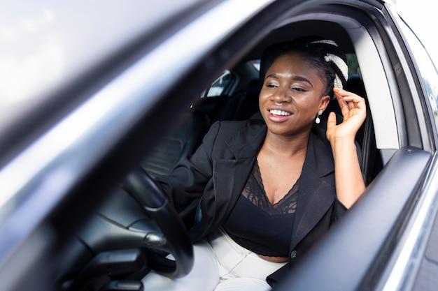 Счастливая женщина за рулем своего личного автомобиля Premium Фотографии