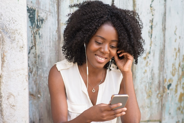Happy woman in earphones enjoying music on phone Free Photo