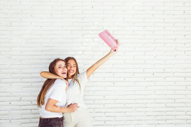 Happy woman embracing her friend and raising her arms with gift Free Photo