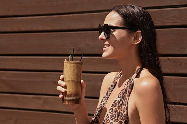 バーでエキゾチックなドリンクを楽しんで、遠くに笑顔を探して、黒いサングラスと水着を着て幸せな女 無料写真