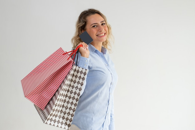 Happy woman enjoying shopping and paying with credit card Free Photo