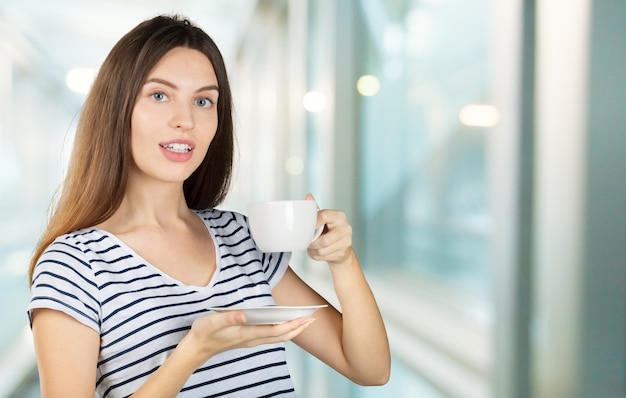 Happy woman enjoying a warm cup of tea or coffee for breakfast Premium Photo