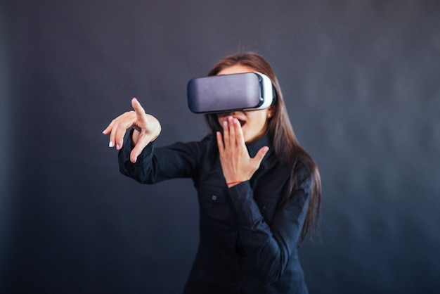Happy woman  gets the experience of using vr-glasses virtual reality headset. Premium Photo