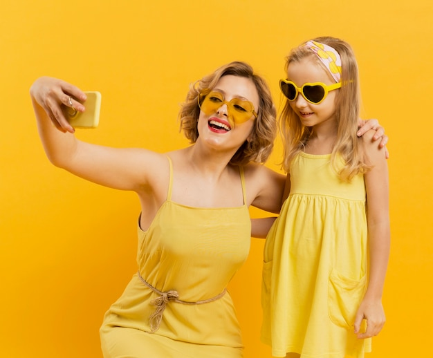 Happy woman and girl taking a selfie while wearing sunglasses Free Photo