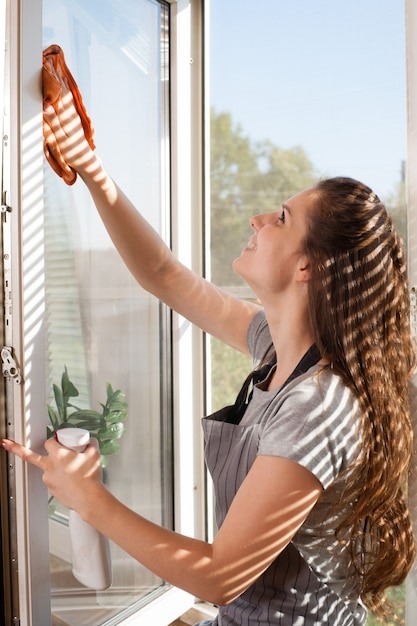 Happy woman in gloves cleaning window with rag and cleanser spray at home Premium Photo