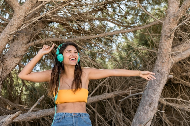 Happy woman in headset listening to music in forest Free Photo