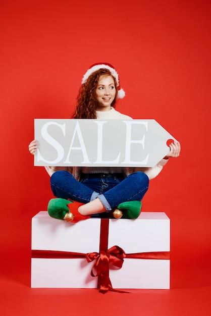 クリスマスセールのバナーを保持している幸せな女性 無料写真