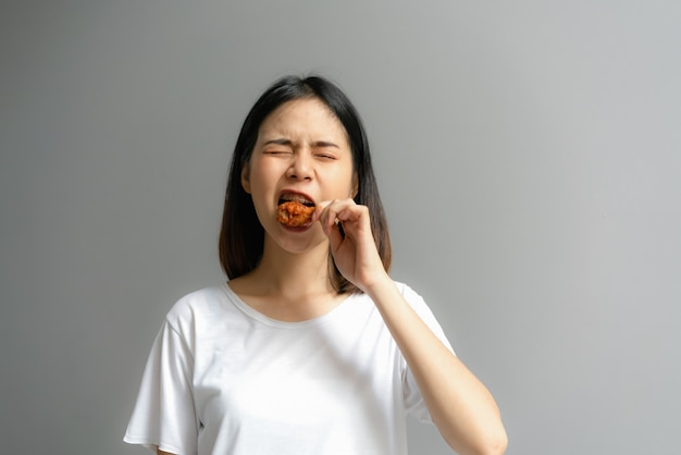 Happy woman holding fried chicken for eat. Premium Photo