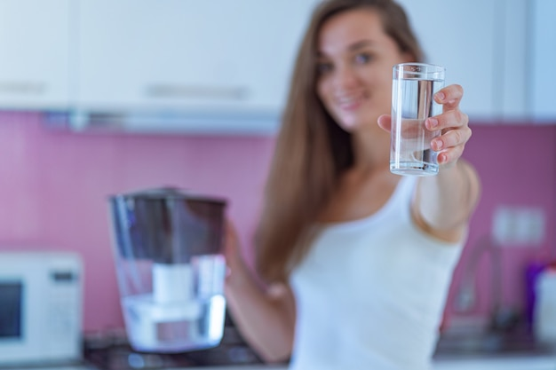 Happy woman holding glass of purified water in the kitchen at home Premium Photo