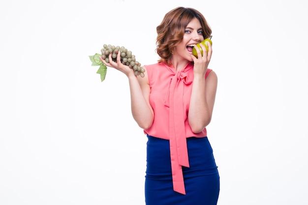 Счастливая женщина держит виноград и ест грушу Premium Фотографии