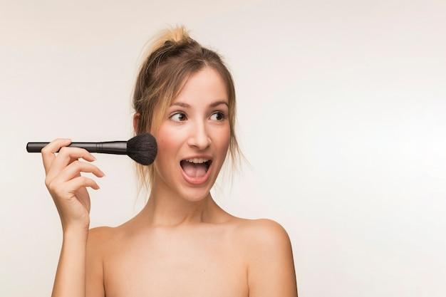 Happy woman holding makeup brush Free Photo
