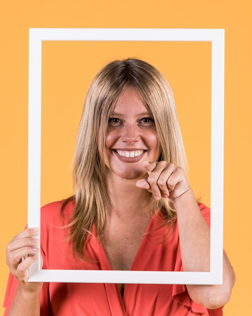 Happy woman holding picture frame in front of her face and pointing index finger towards the camera Free Photo
