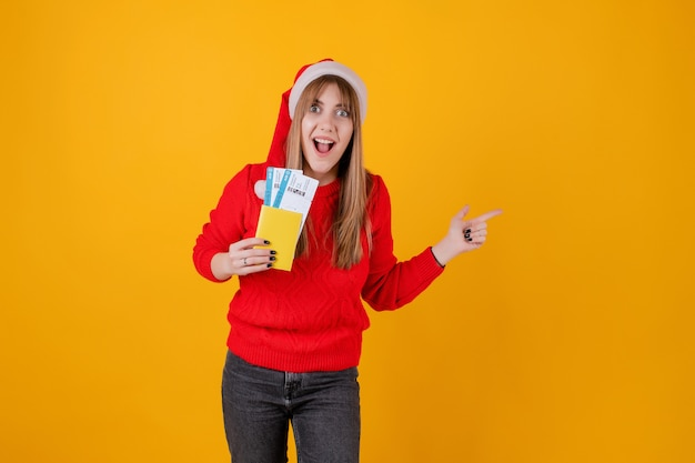 Happy woman holding plane tickets and passport wearing santa hat Premium Photo