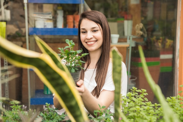 Happy woman holding potted plants in greenhouse Free Photo