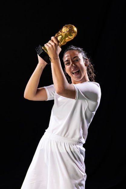 Happy woman holding soccer trophy Free Photo
