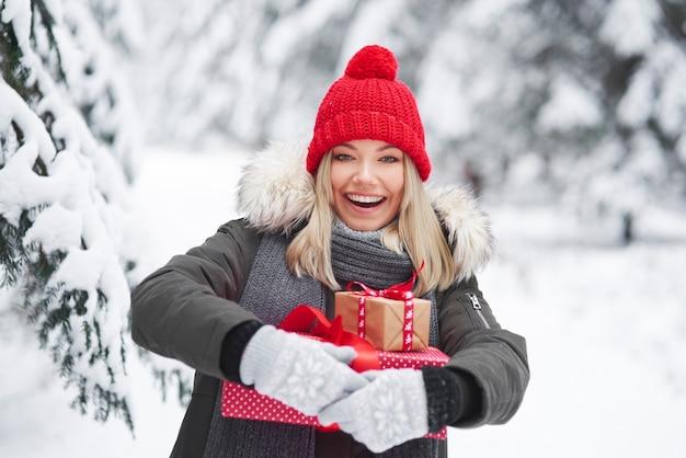 Donna felice che tiene pila di regali di natale Foto Gratuite