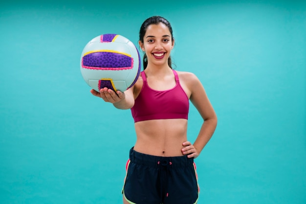 Happy woman holding a volley ball Free Photo