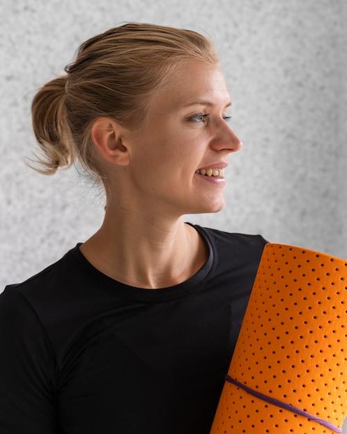 Stuoia di yoga della holding della donna felice Foto Gratuite