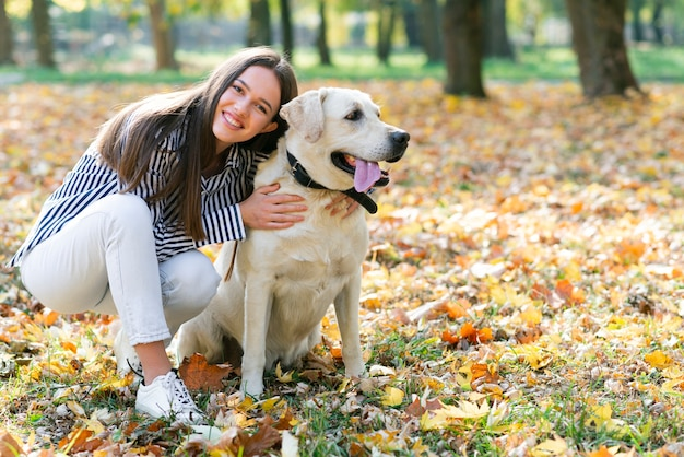 Happy woman hugging her dog in the park Free Photo